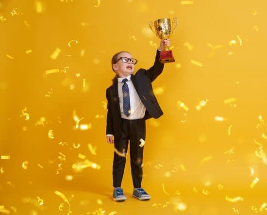 Little child is winner. Kid on the background of bright yellow wall. Smart power concept. Golden confetti and the Cup for first place.