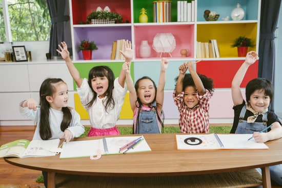 Group of little preschool kids hands up in class . portrait of children diversity education concept.