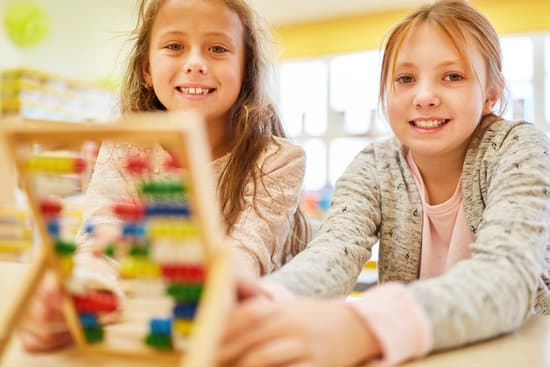 Two girls as elementary school students are calculating with the abacus