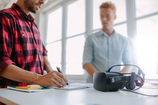 Shot of two young man standing at a table with VR goggles writing on notepad. Developers testing virtual reality glasses in office.